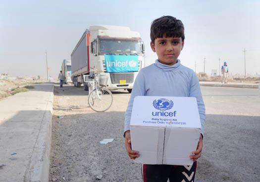 Pojke håller i en kartong med hygienpaket