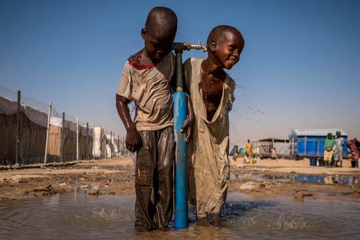Barn leker vid en vattenkran